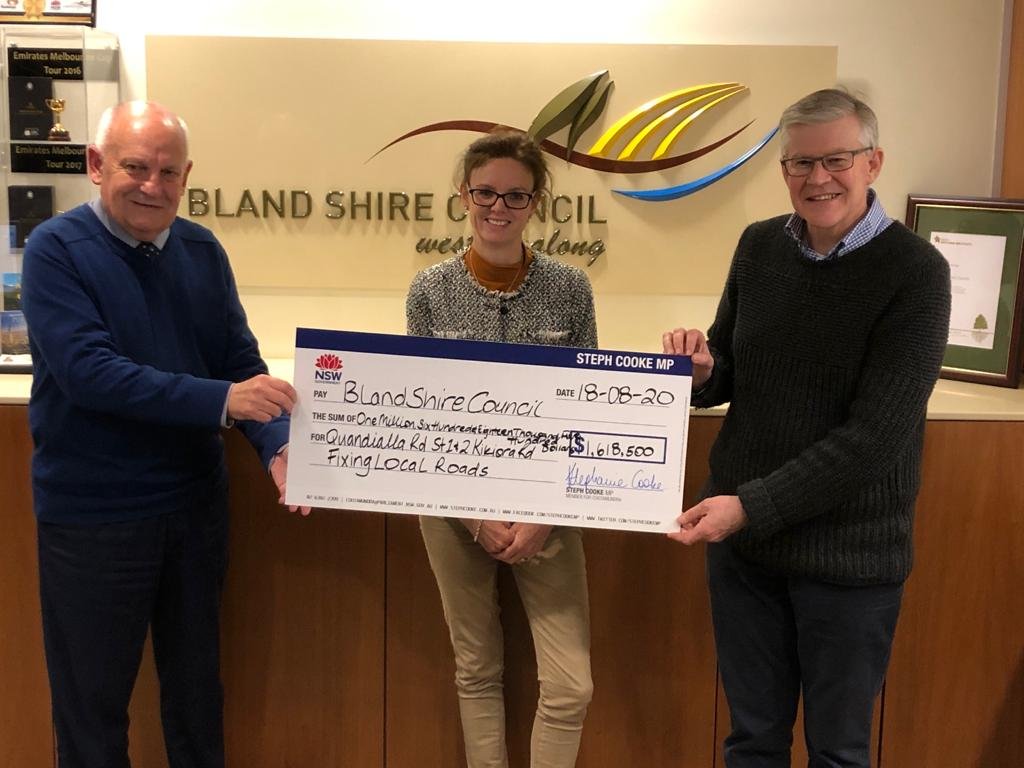 Ray Smith, Steph Cooke MP and Cr Brian Monaghan hold a large cheque in the Bland Shire office.