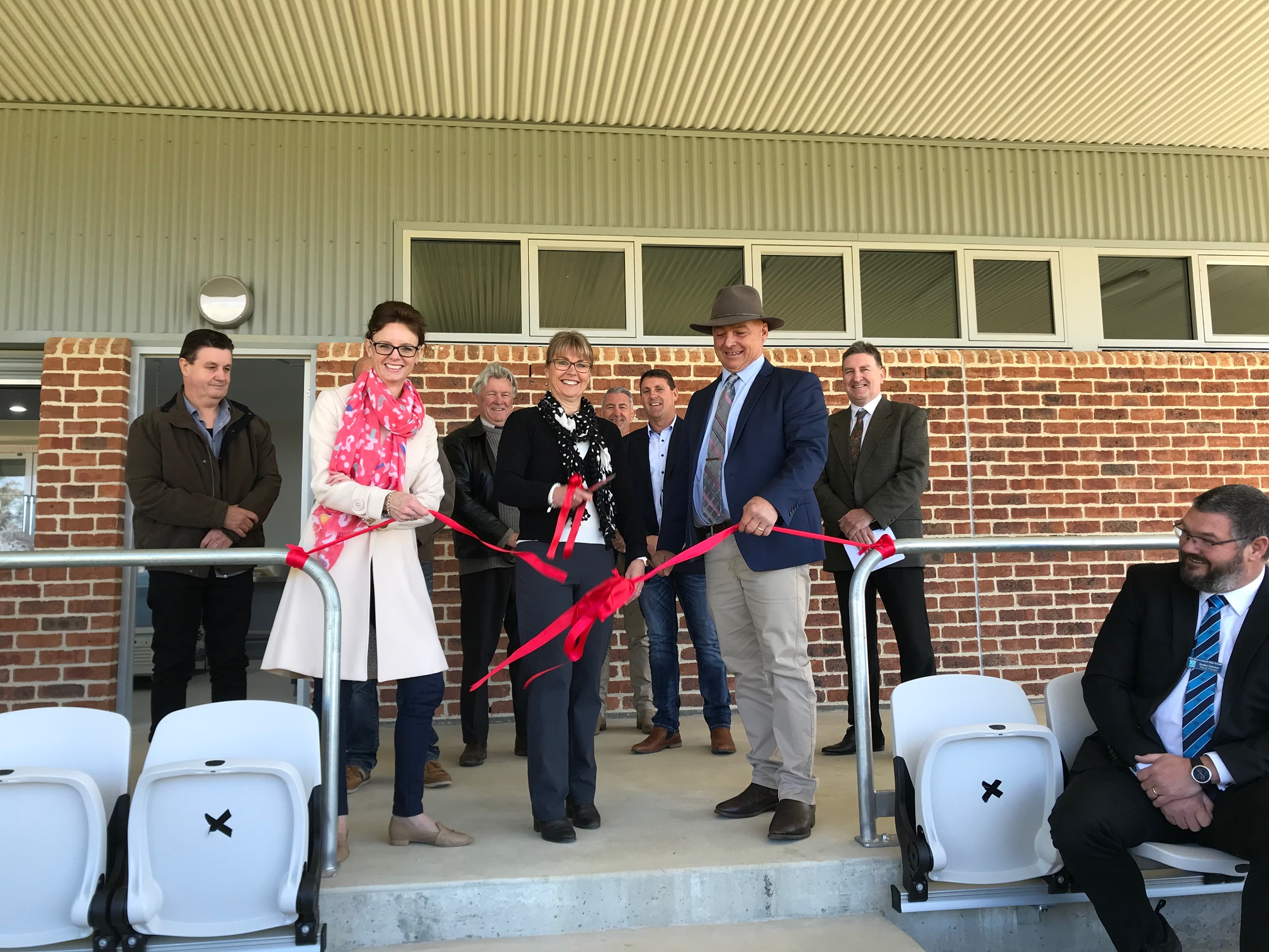 Steph Cooke, Mayor Mark Liebich and others cut a red ribbon to open the grandstand.