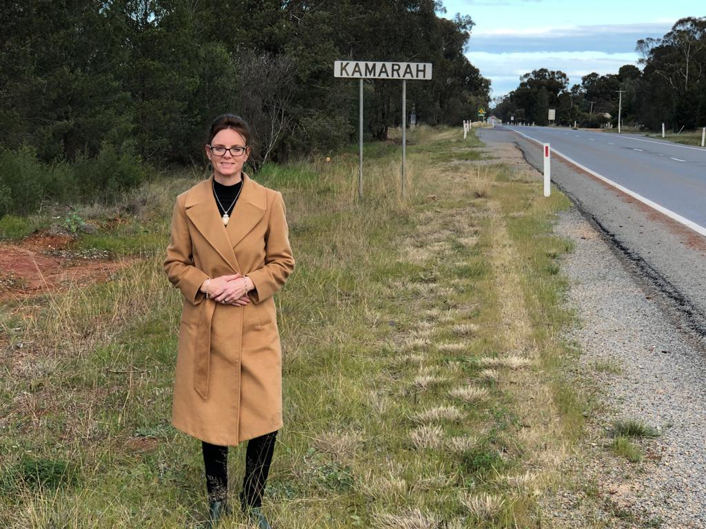 Steph Cooke stands beside a road. A sign says Kamarah behind her.