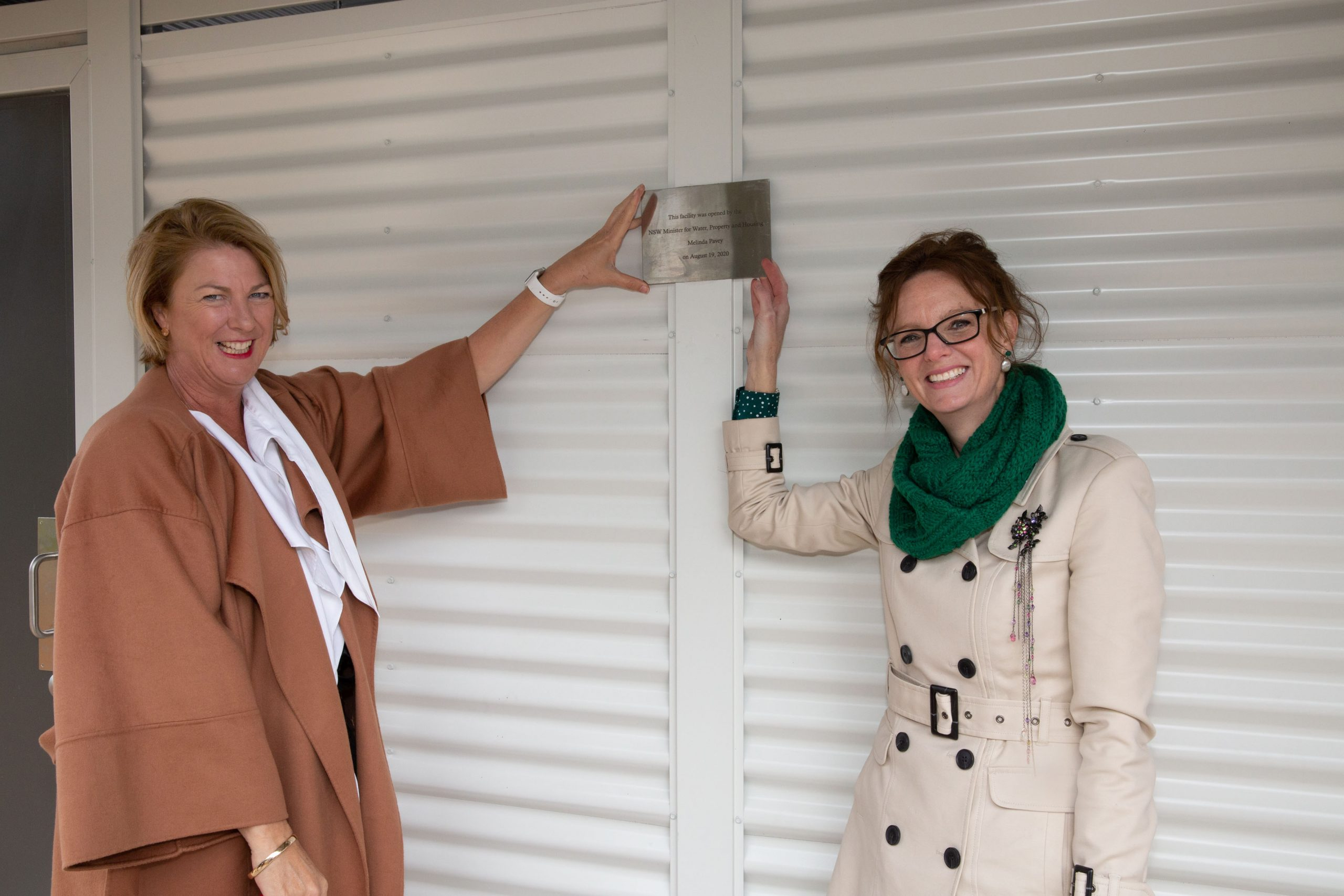 Melinda Pavey and Steph Cook touch a new plaque and smile at the camera.