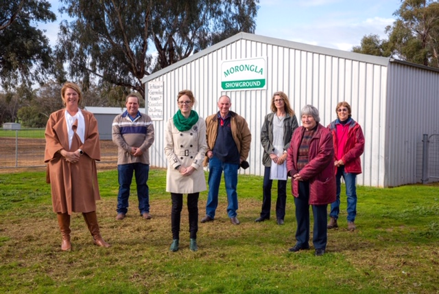 Minister Pavey, David Langfield, Steph, Graham Wallace, Lyn Harvey, Barbara Langfield and Julie Whitby stand in front of a shed with a green 'Morongla Showground' sign