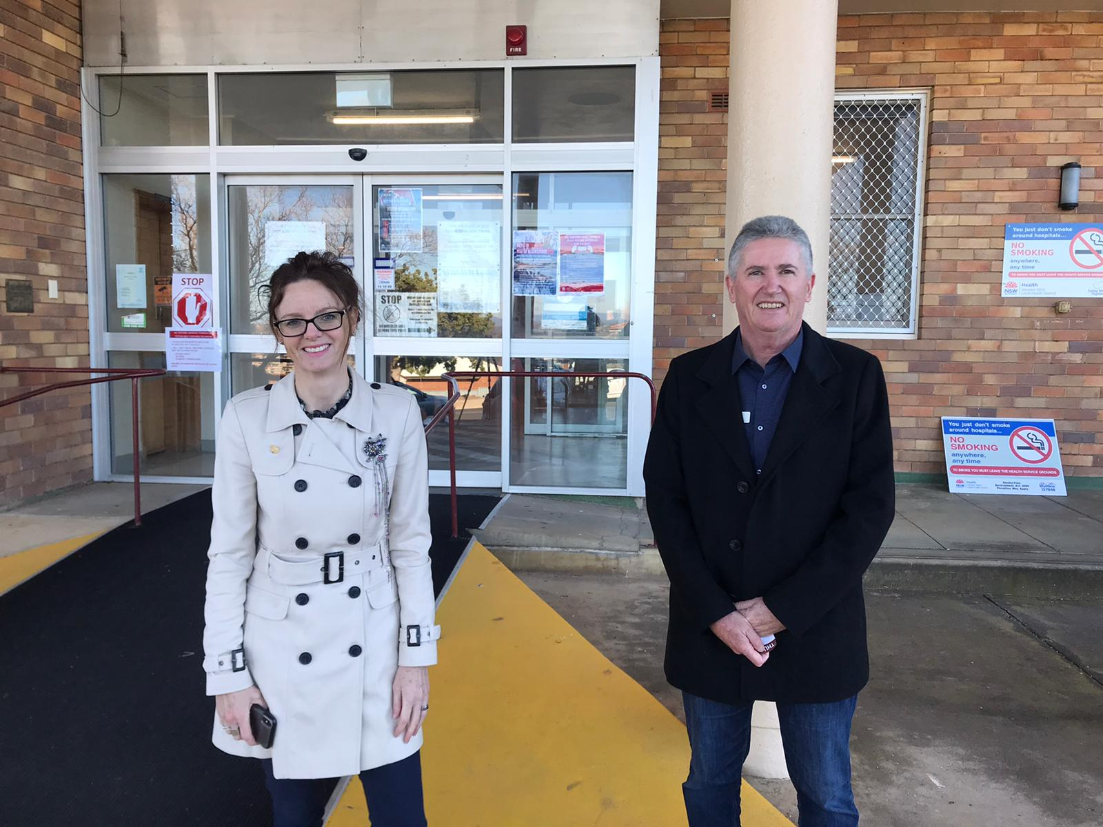 Steph Cooke MP and Robert Mills stand in front of the Cowra Hospital. They both wear jackets and smile at the camera.
