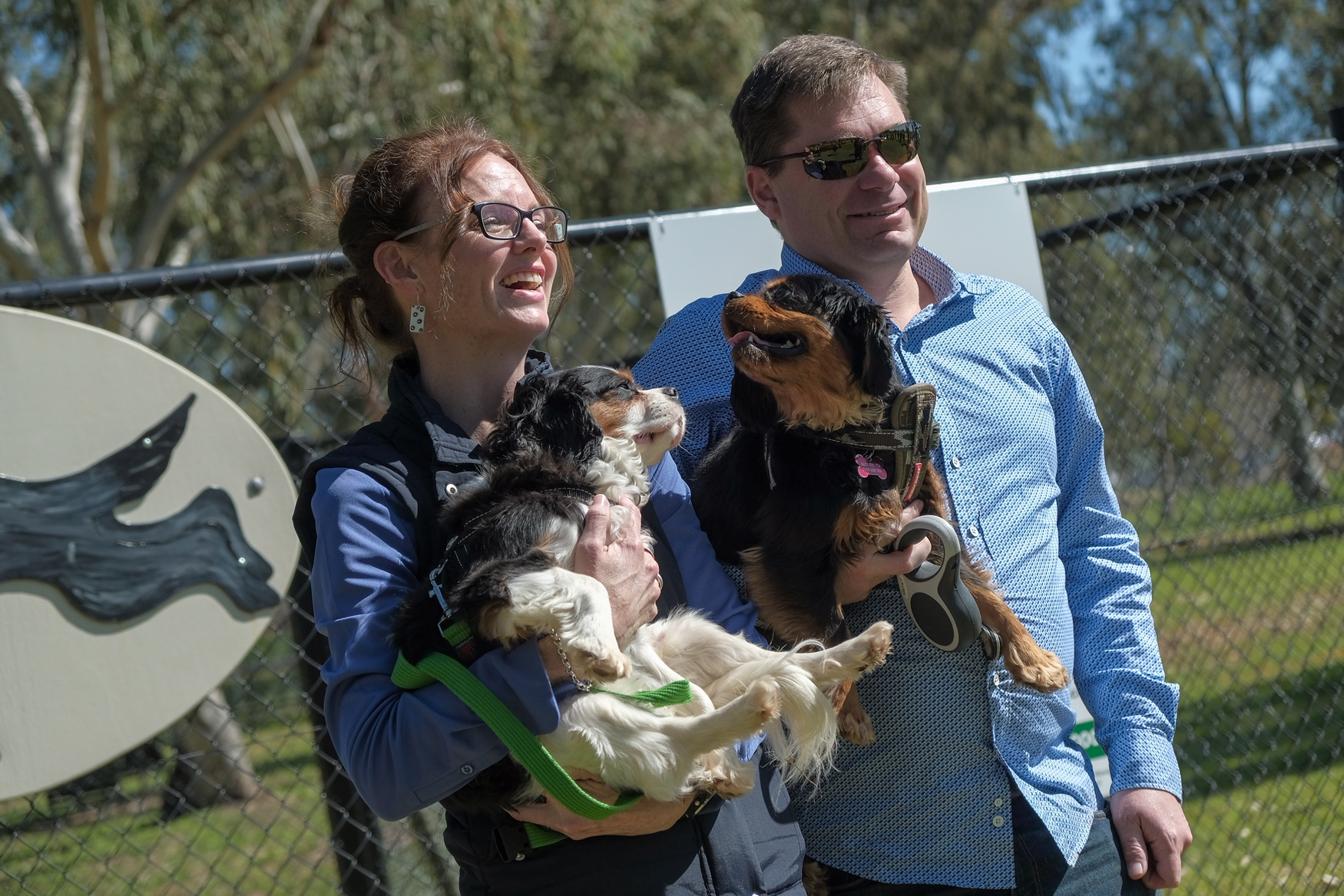 Steph Cooke and Keith Duran hold their dogs at the Junee dog park.