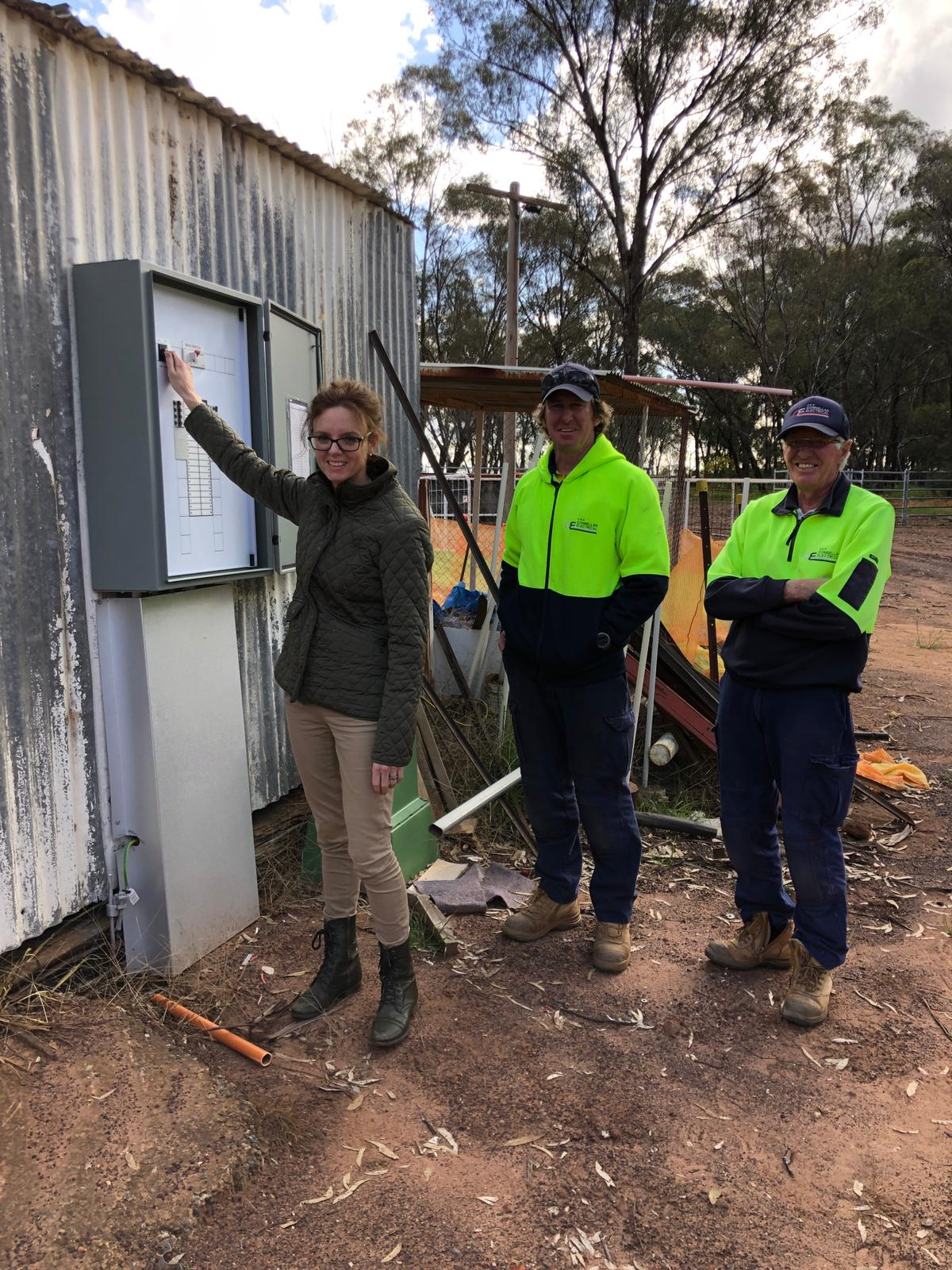 Steph Cooke MP with contractors Andrew and Garry Conlon at the rodeo ground. They stand in front of a new electrical box.