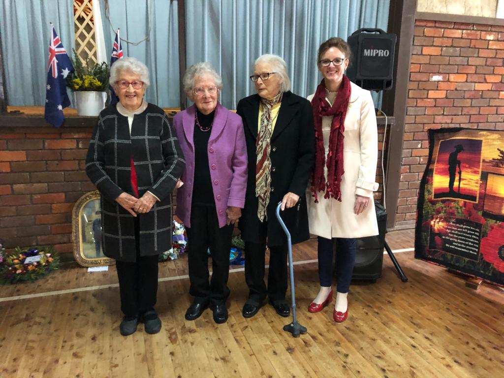 Jean Maitland, Betty Lawrence and Patricia Wells with Steph Cooke in the Barmedman hall. They stand in front of Australian flags and pictures of servicemen in uniform.