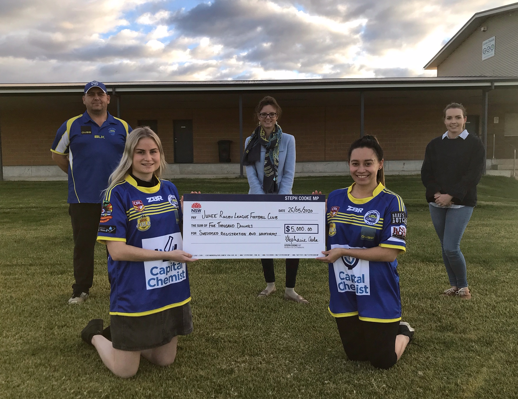 Steph Cooke MP stands behind a large cheque held by two women kneeling in football uniforms.