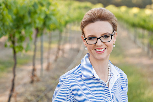 Steph Cooke stands in a vineyard and smiles at the camera.