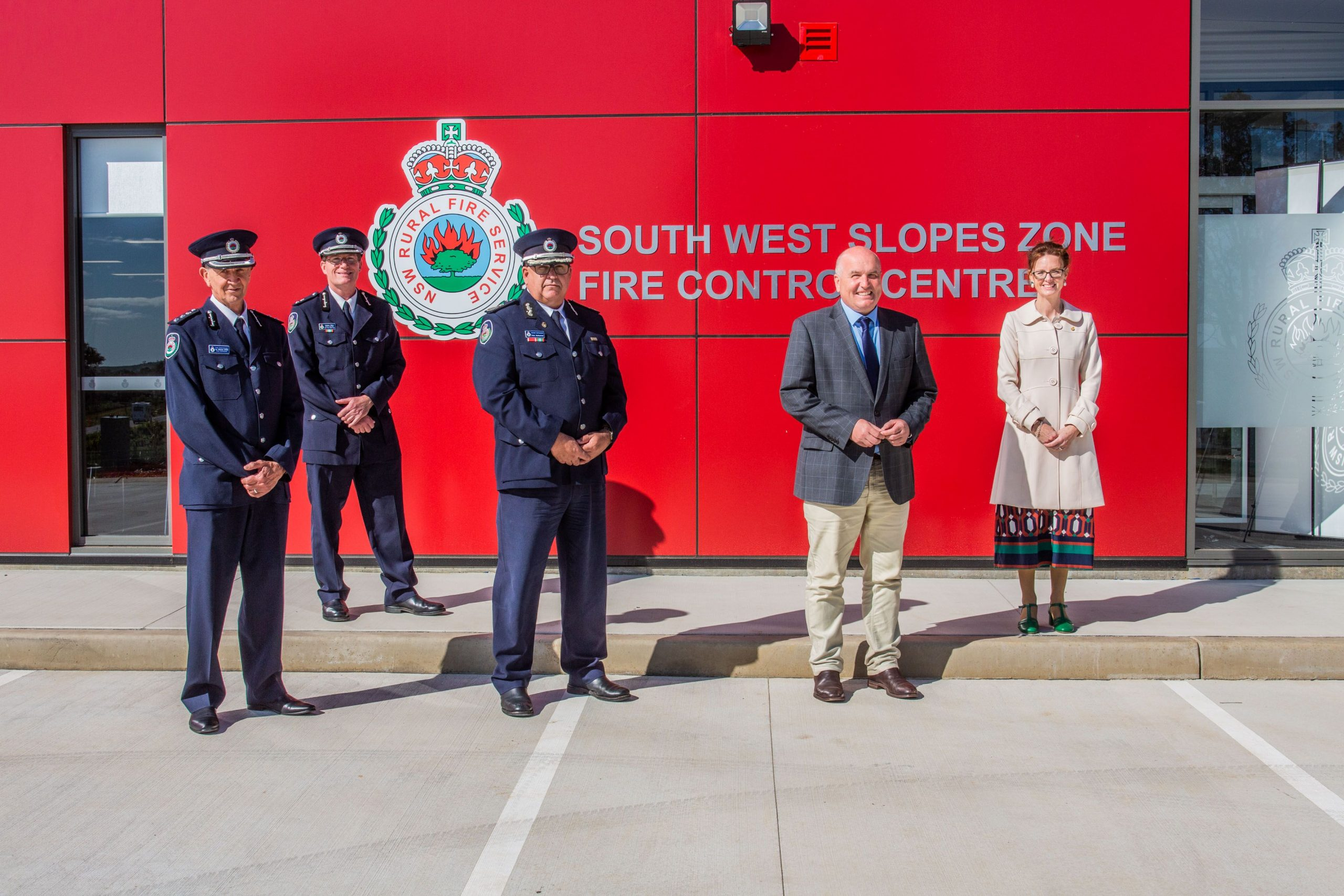RFS Representatives, Minister Elliott and Steph Cooke stand in front of the bright red front of the fire control centre.