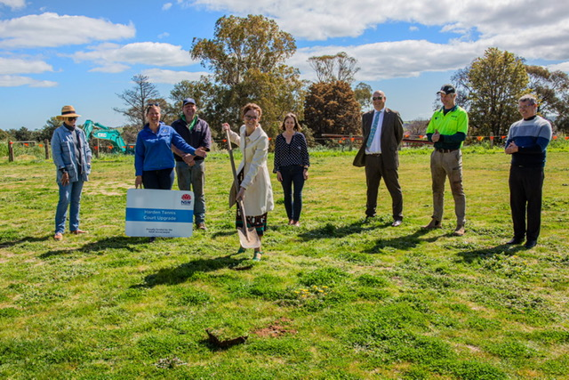 Steph Cooke holds a shovel over green grass and is surrounded by community members. All laugh and smile at Steph or the camera.