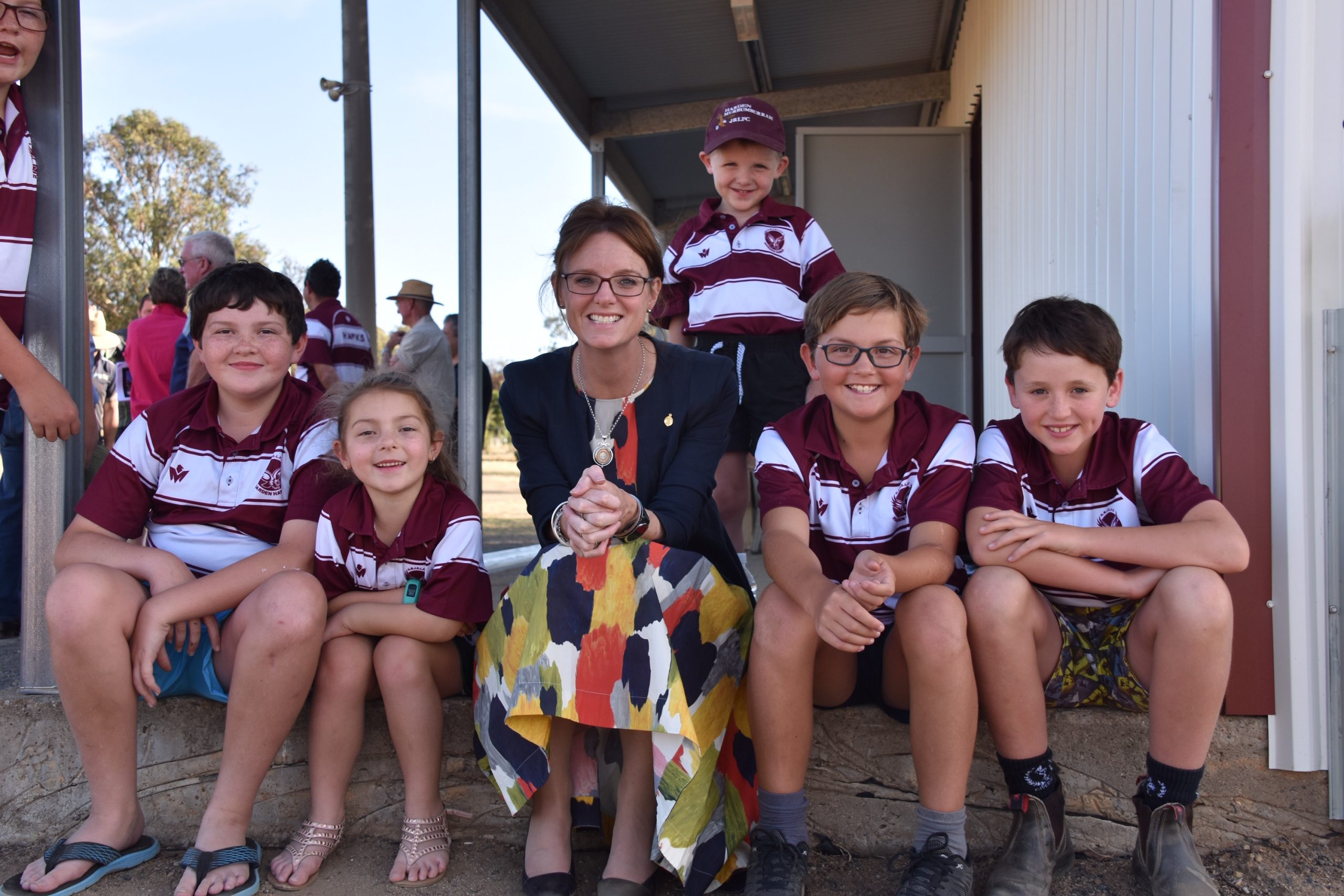 Steph Cooke sits with four players from the junior rugby league club in their uniforms, while another stands behind Steph. They sit on a step and smile at the camera.