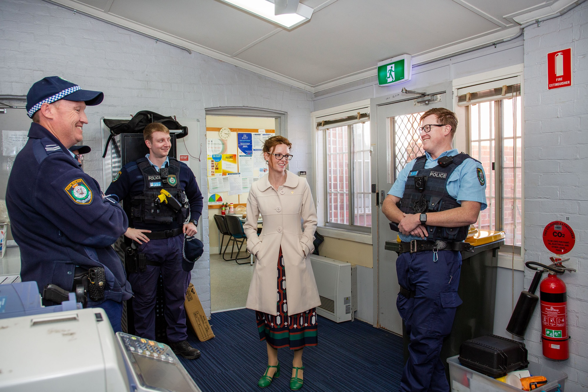 Steph Cooke speaks with police officers. They lean against walls and smile.