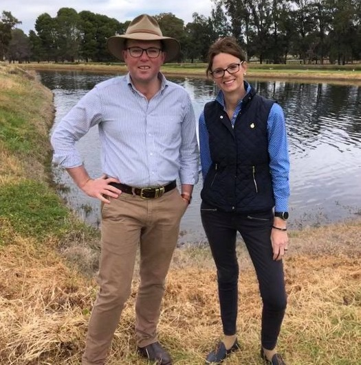 Minister Adam Marshall and Steph Cooke stand in front of a waterway and smile at the camera.