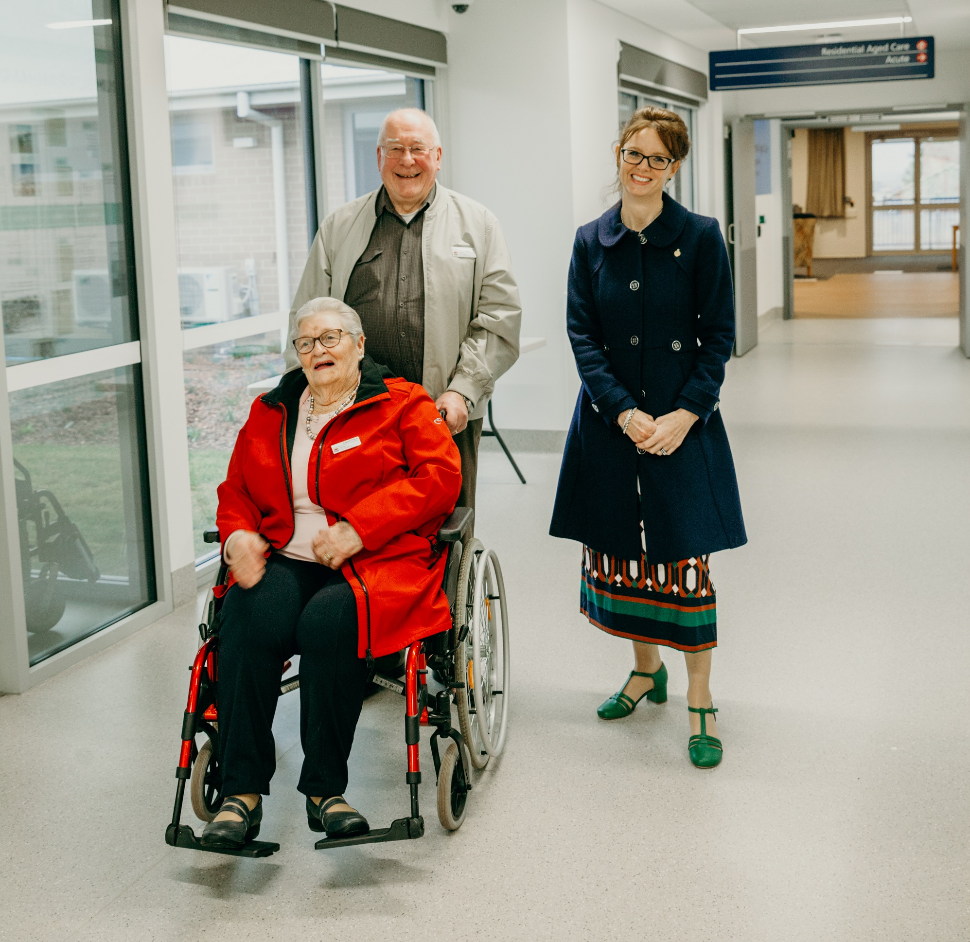 A woman in a wheelchair and an elderly man pushing her stand next to Steph Cooke in a hospital corridor.