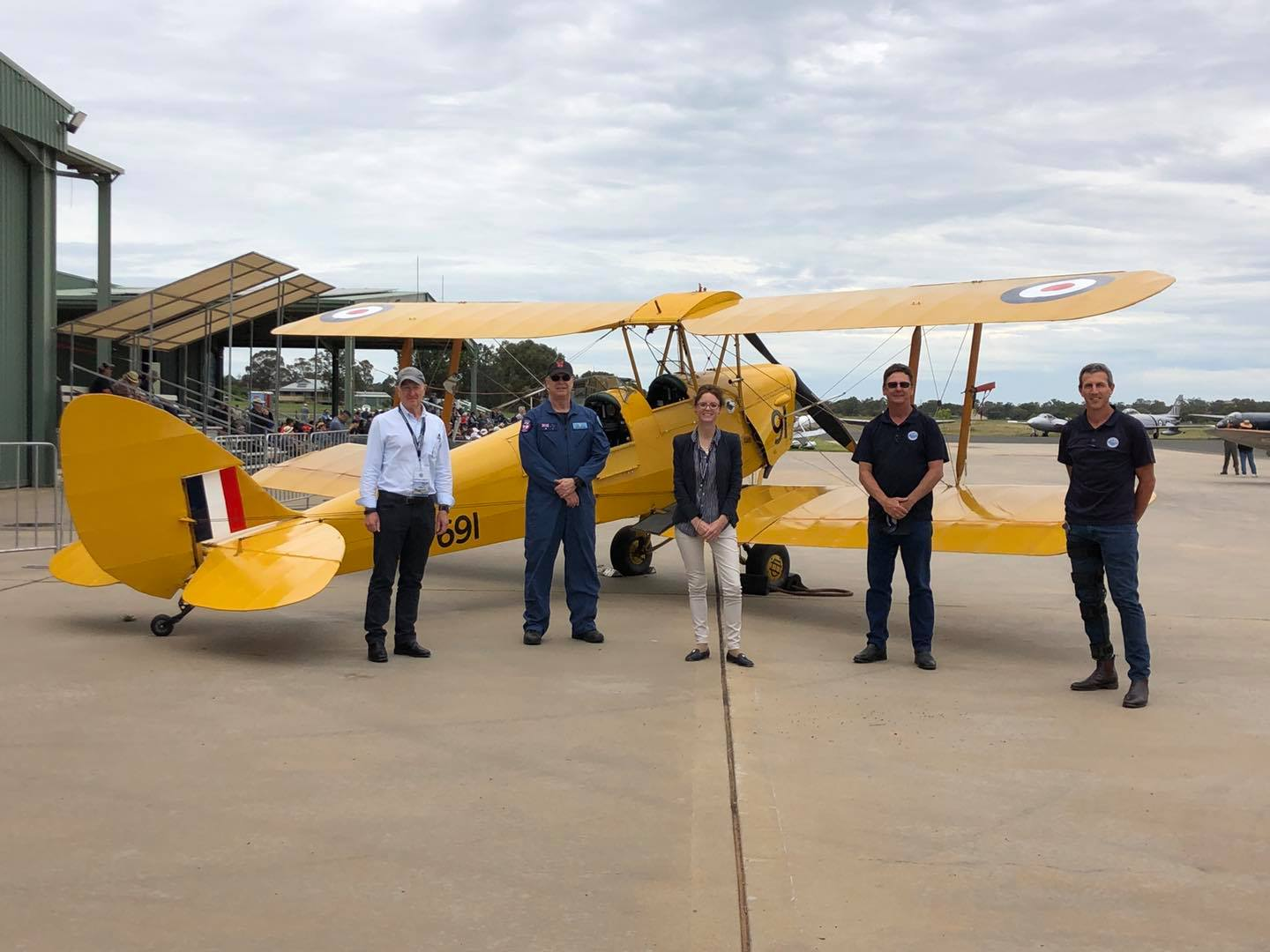 Steph Cooke stands in front of a bi plane with four men.