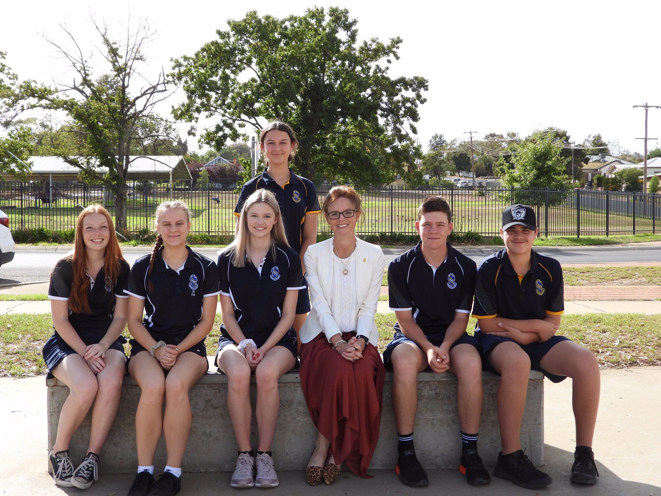 Steph Cooke MP sits with Junee High School students on a large concrete bench.