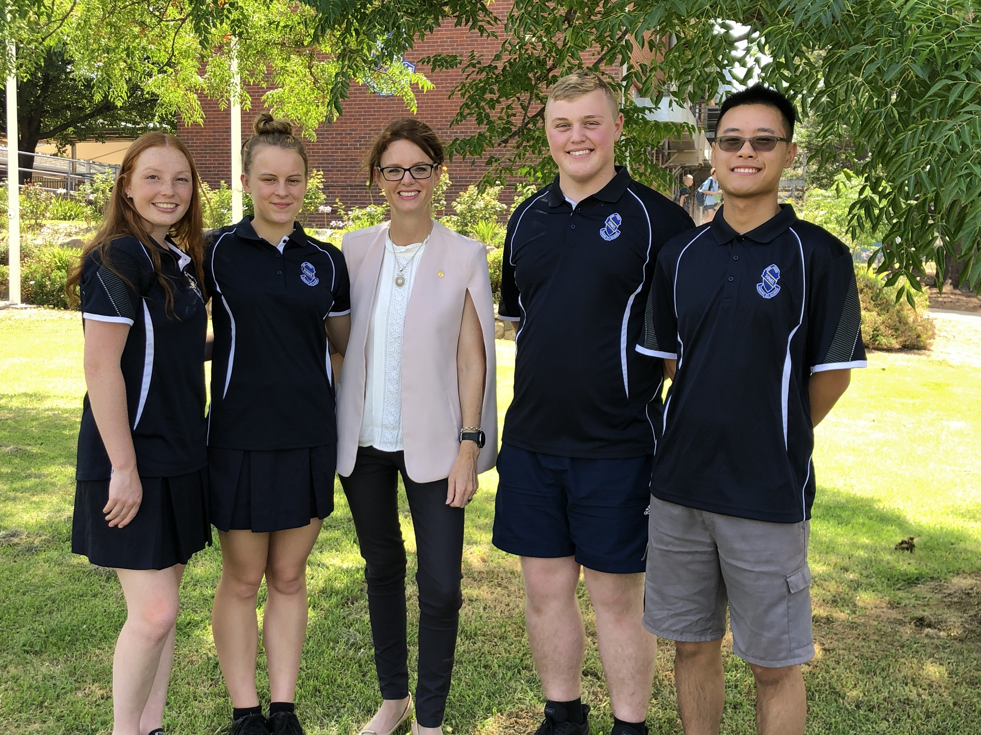 Two female school students and two male students wear their uniforms and stand around Steph Cooke. They are under a shady tree and smile at the camera.