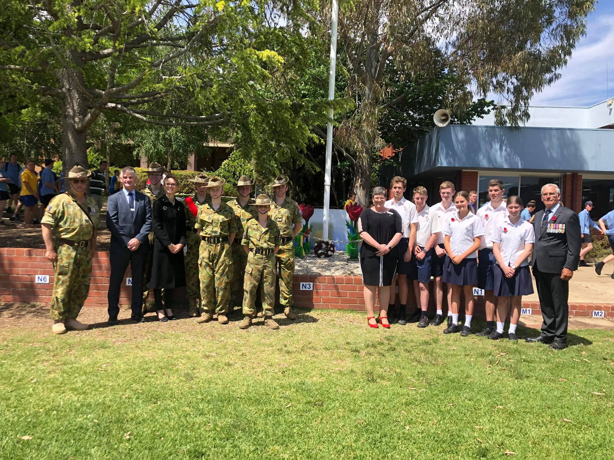 A group of high school students in uniform and in cadet army uniforms stand with Steph Cooke and teachers around a flag pole. All wear red poppies on their shirts.