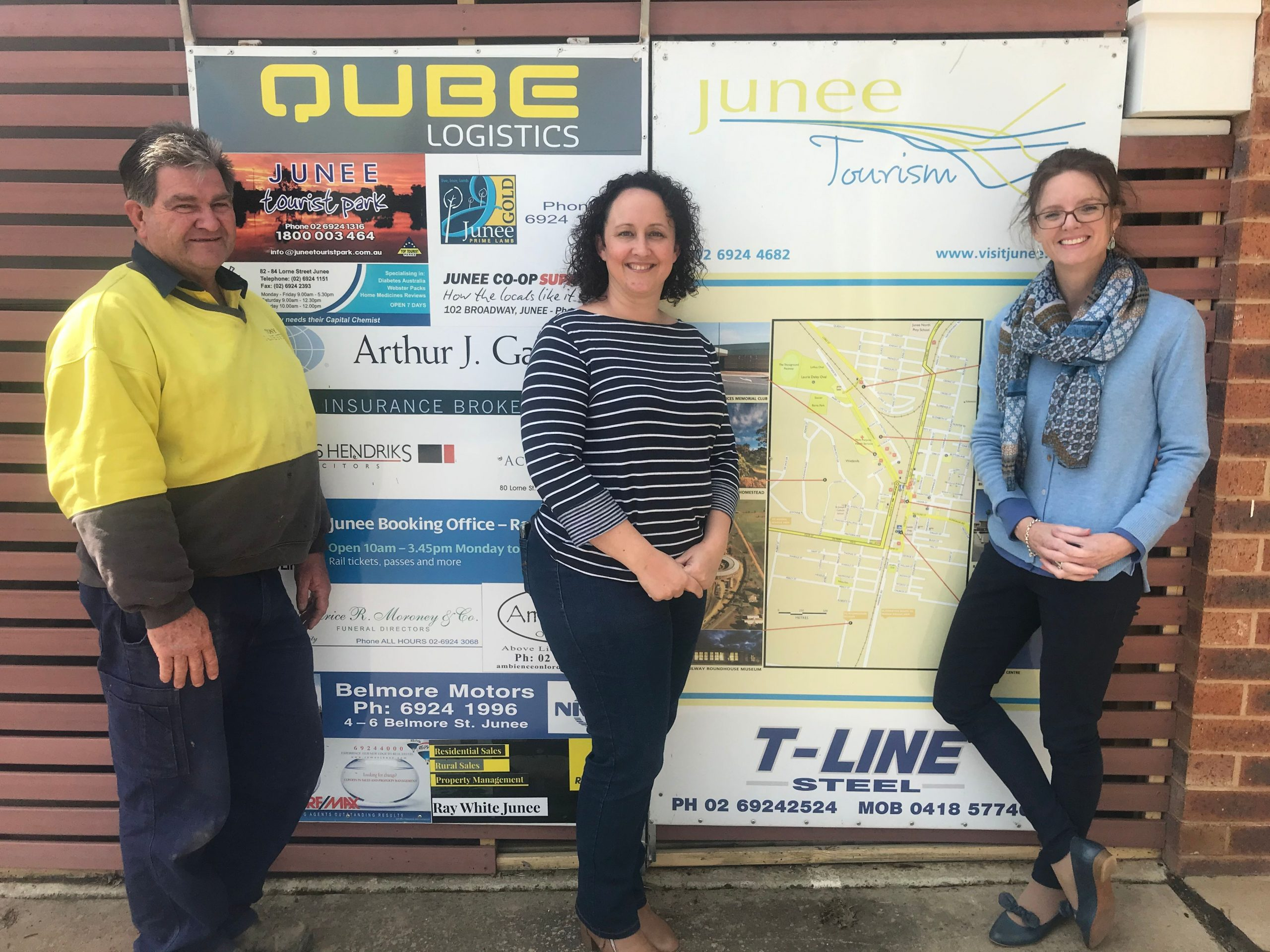 Tony Butt, Natalie Phillips from Junee Business and Trades with Steph Cooke MP leane against a tourism map of Junee and smile at the camera.