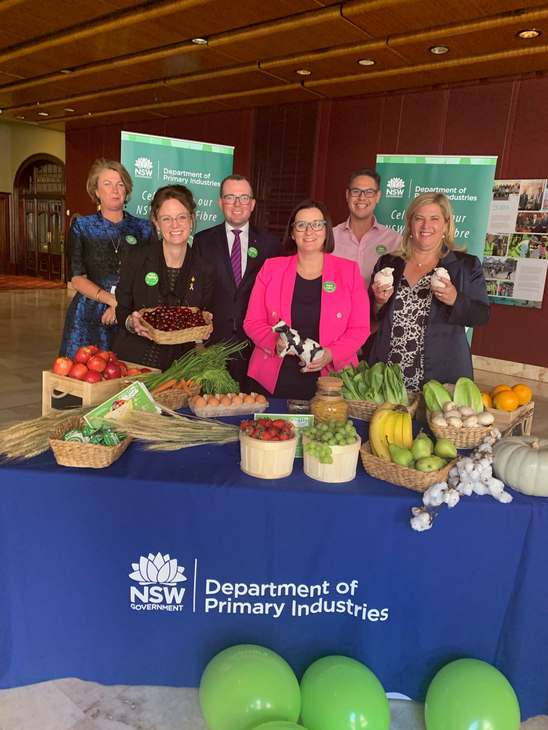 Minister Melinda Pavey, Steph Cooke MP, Minister Adam Marshall, Minister Sarah Mitchell, Wes Fang MLC and Minister Bronnie Taylor hold fruit, vegetables and plastic cows while standing behind a table covered in fruit, vegetables and eggs.