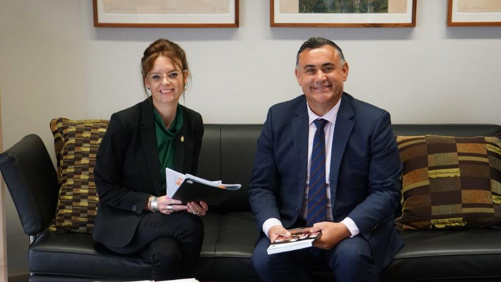 Steph Cooke and John Barilaro sit on a couch and hold Budget papers. They smile at the camera and wear suits.