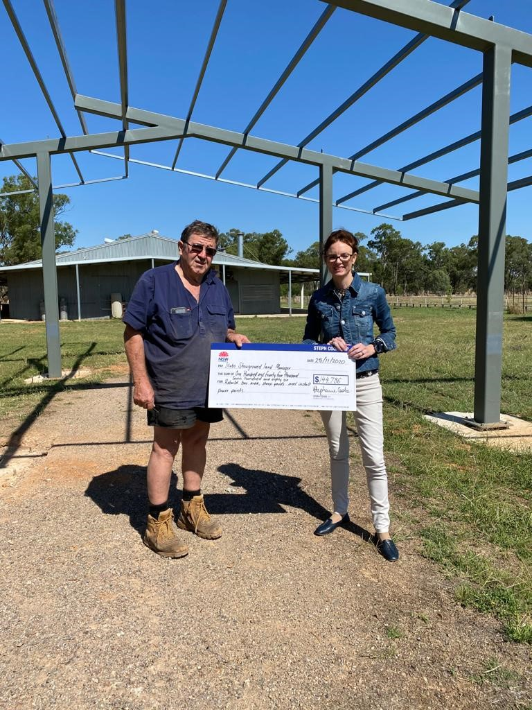 David Carter holds one end of a large cheque with Steph Cooke holding the other end. They stand under a metal frame and smile at the camera.