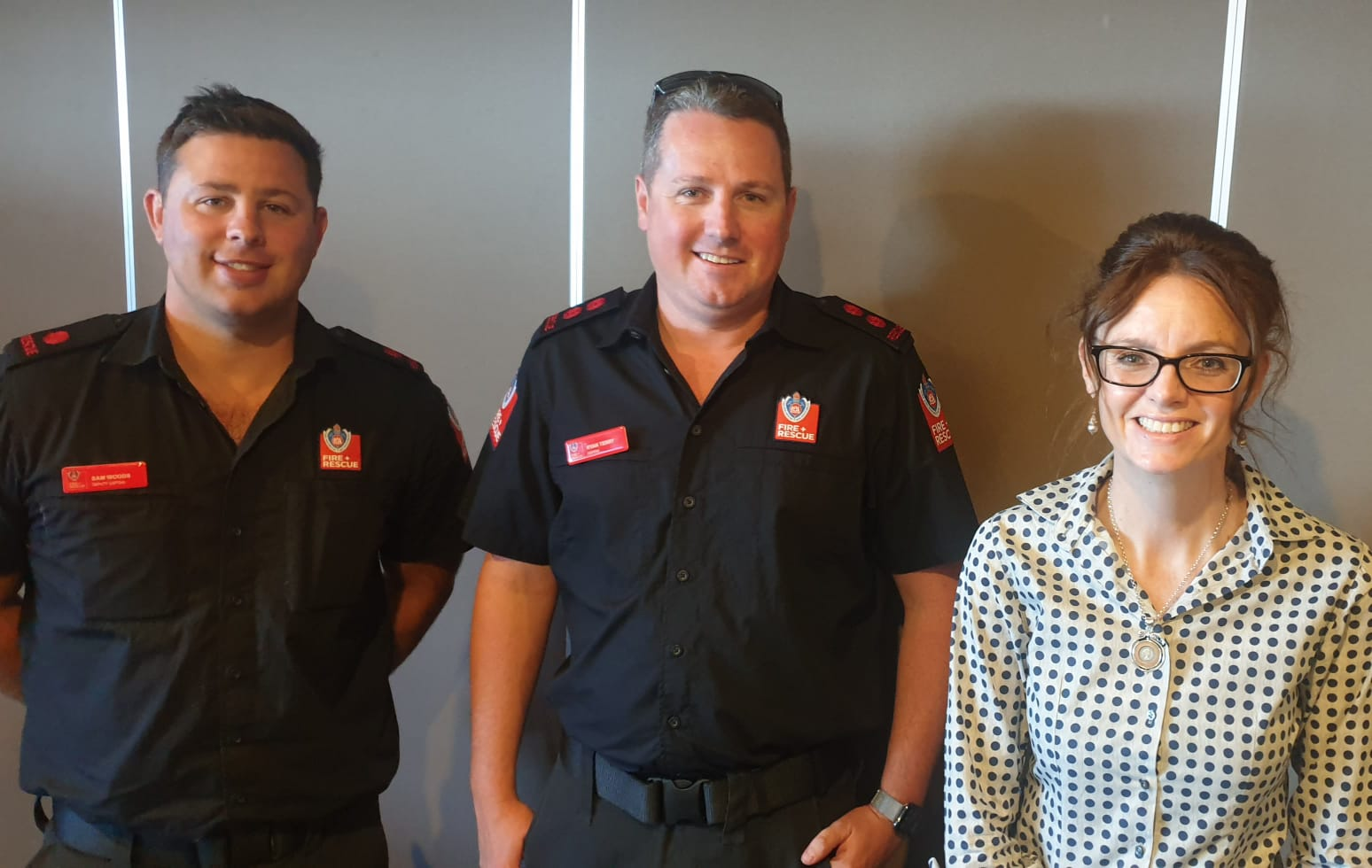 Deputy Captain Sam Woods, Captain Ryan Terry and Steph Cooke MP stand side by side and smile at the camera. Sam and Ryan wear fire and rescue uniforms.