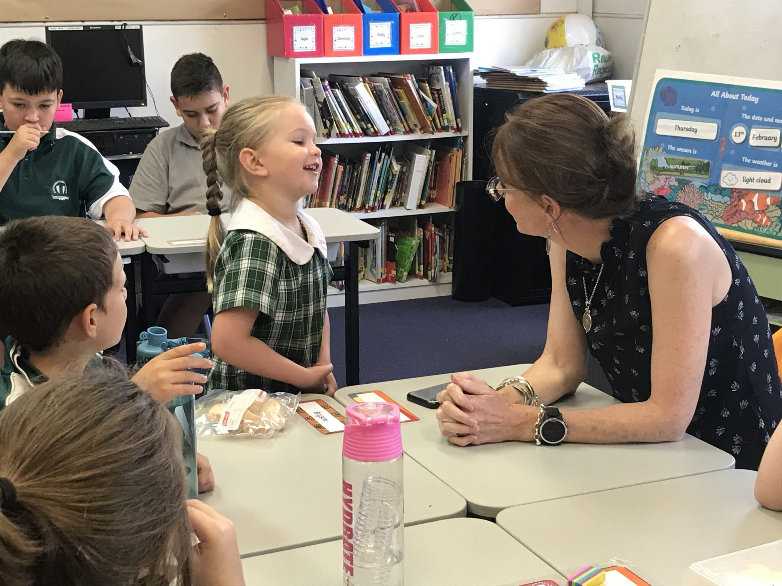 A primary school student laughs and smiles at Steph Cooke, who sits at a primary-sized desk in a classroom.