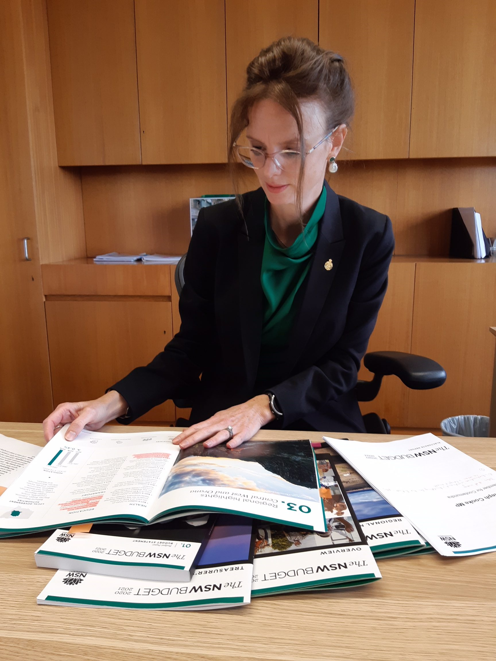 Steph Cooke looks down at Budget Papers spread across a timber desk.