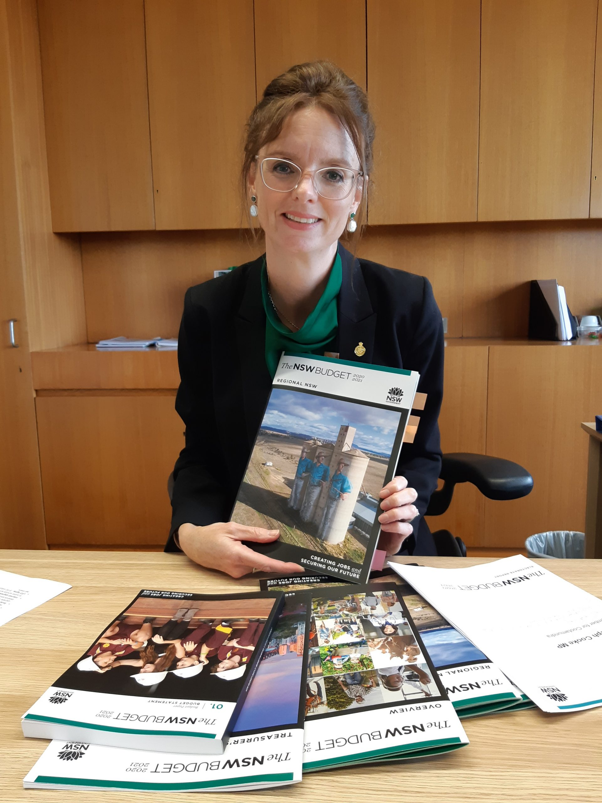 Steph Cooke sits at a timber desk with budget papers in front of her. She holds budget papers and smiles at the camera.