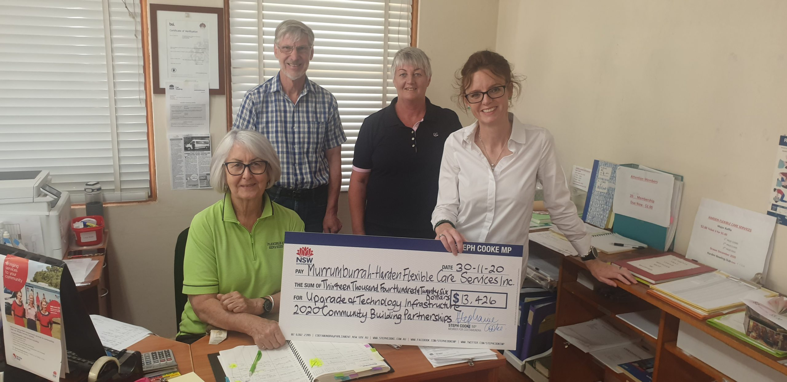 Trish Shea, Stewart Bruce, Jacinta Potts and Steph Cooke MP hold a large cheque in an office. Surrounding them is paperwork and files.