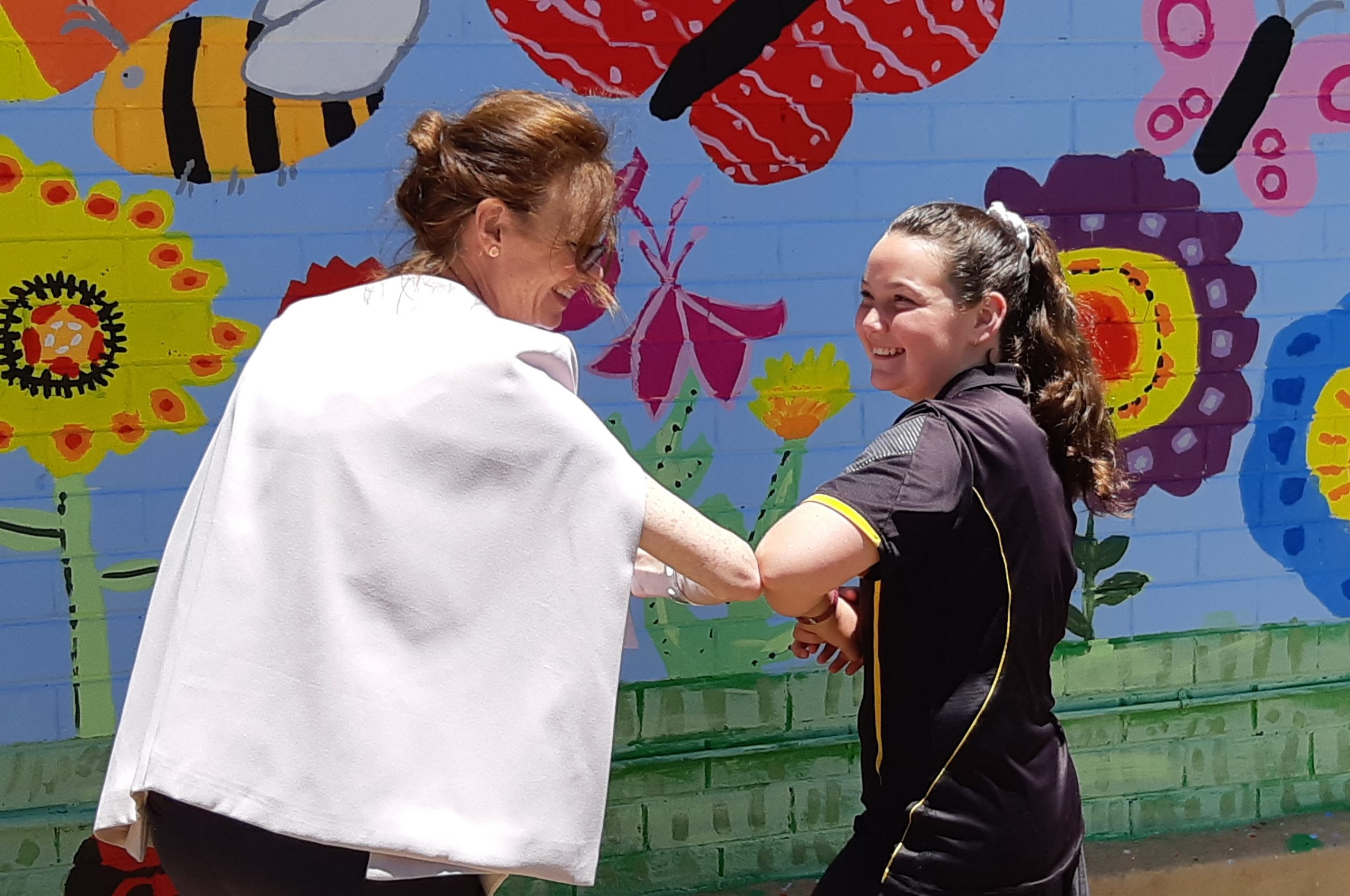Steph Cooke and a female student bump elbows in front of a brightly painted wall with large flowers, butterflies and bees.