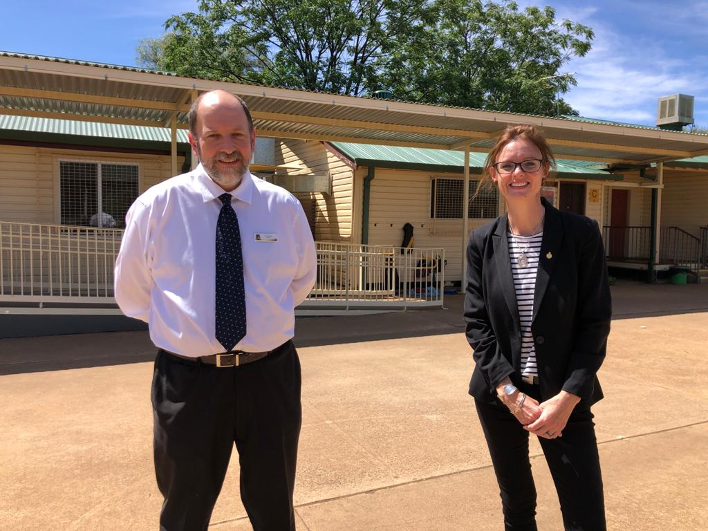 Paul Laing and Steph Cooke smile at the camera. They stand in a concrete courtyard and classrooms can be seen behind them.