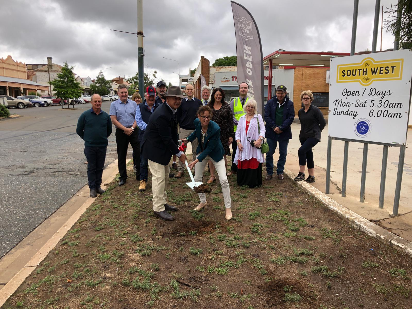 Cr Mark Liebich and Steph Cooke MP lift a shovel with earth together. People stand behind them looking on.