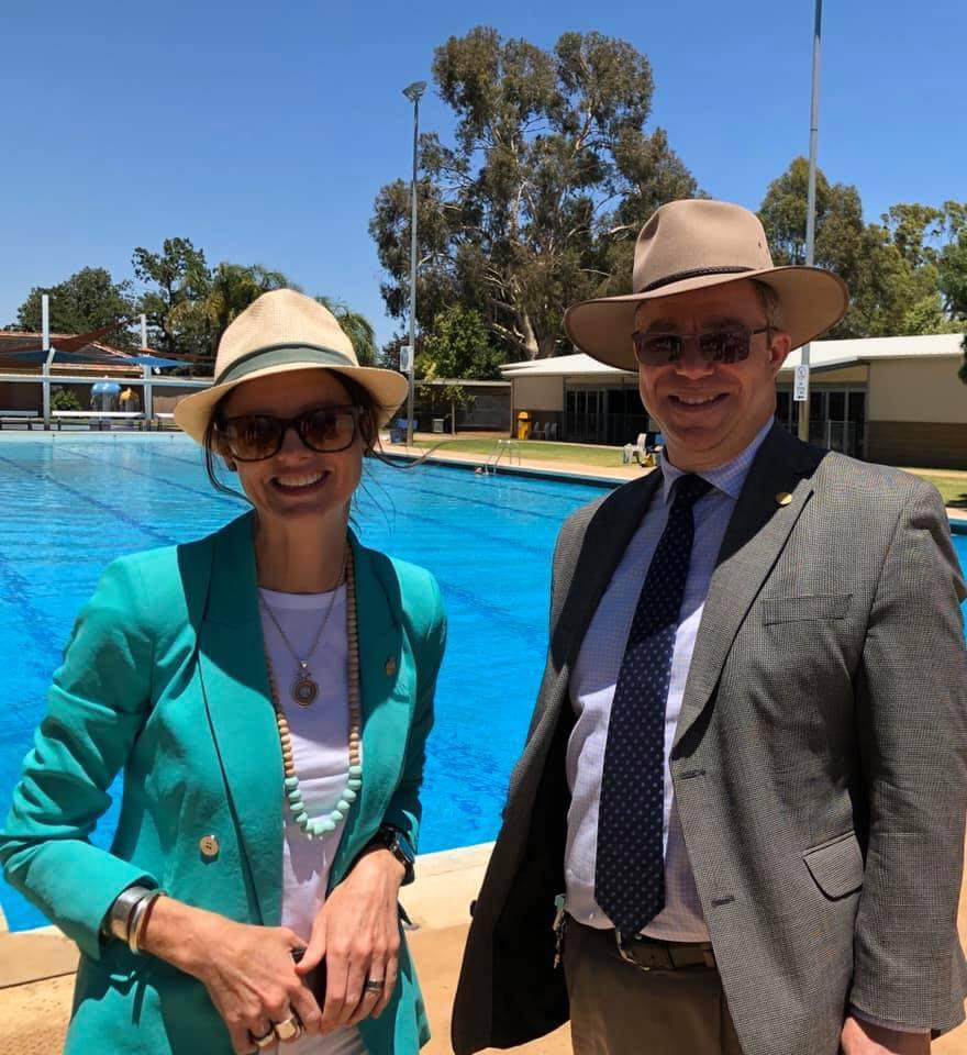 Steoh Cooke and Rick Firman wear hats and sunglasses, they stand in front of a large swimming pool.