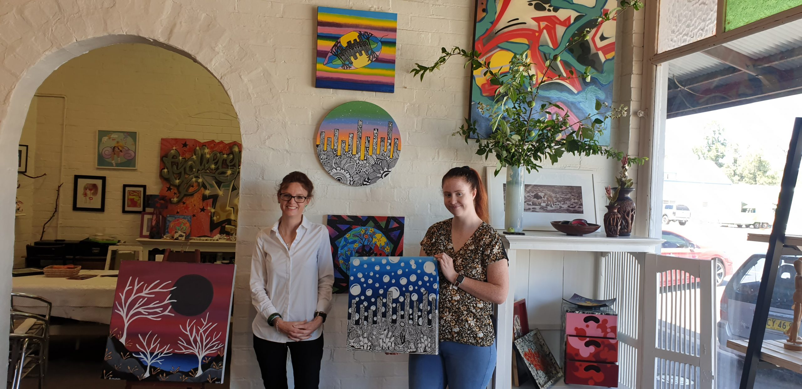 Steph Cooke MP and Zoyie Lee Newham stand in an art gallery surrounded by colourful paintings.