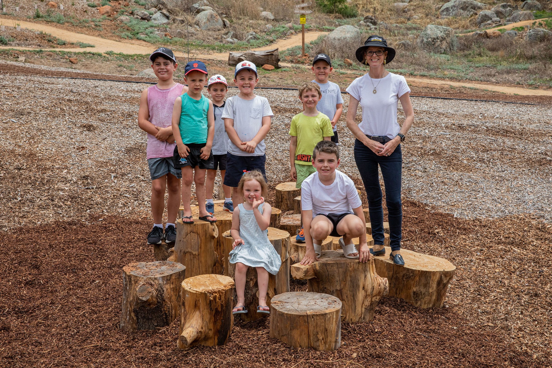 Eight young children and Steph Cooke stand on timber stumps arranged together.