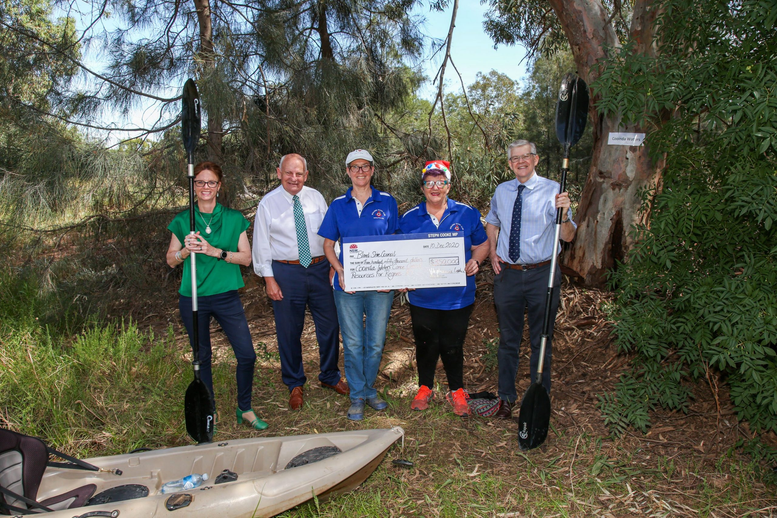 Steph Cooke, Ray Smith, Amanda Stitt, Gail Platz and Brian Monaghan stand in front of trees and a canoe is at their feet. Steph and Brian hold paddles.
