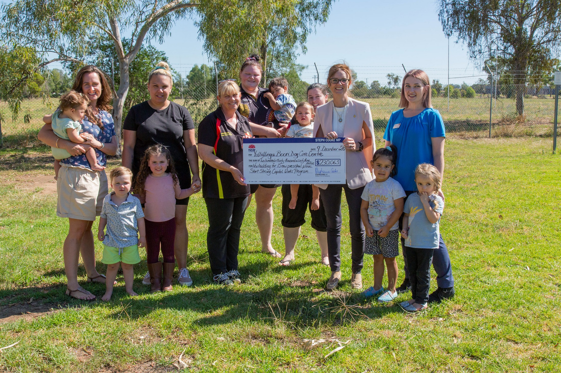 A group of women and small children stand together on grass. In the middle of the group Caroline Bamblett and Steph Cooke MP hold a large cheque.