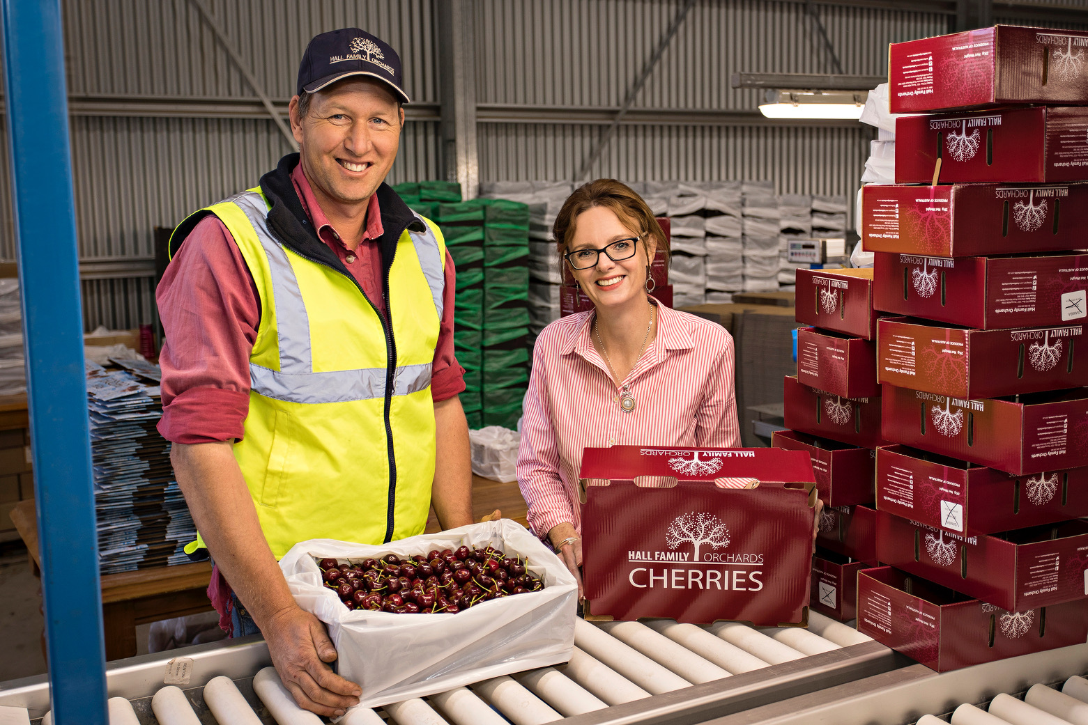 Steph Cooke and a cherry farmer stand in front of a conveyor belt and are surrounded by cherry boxes.