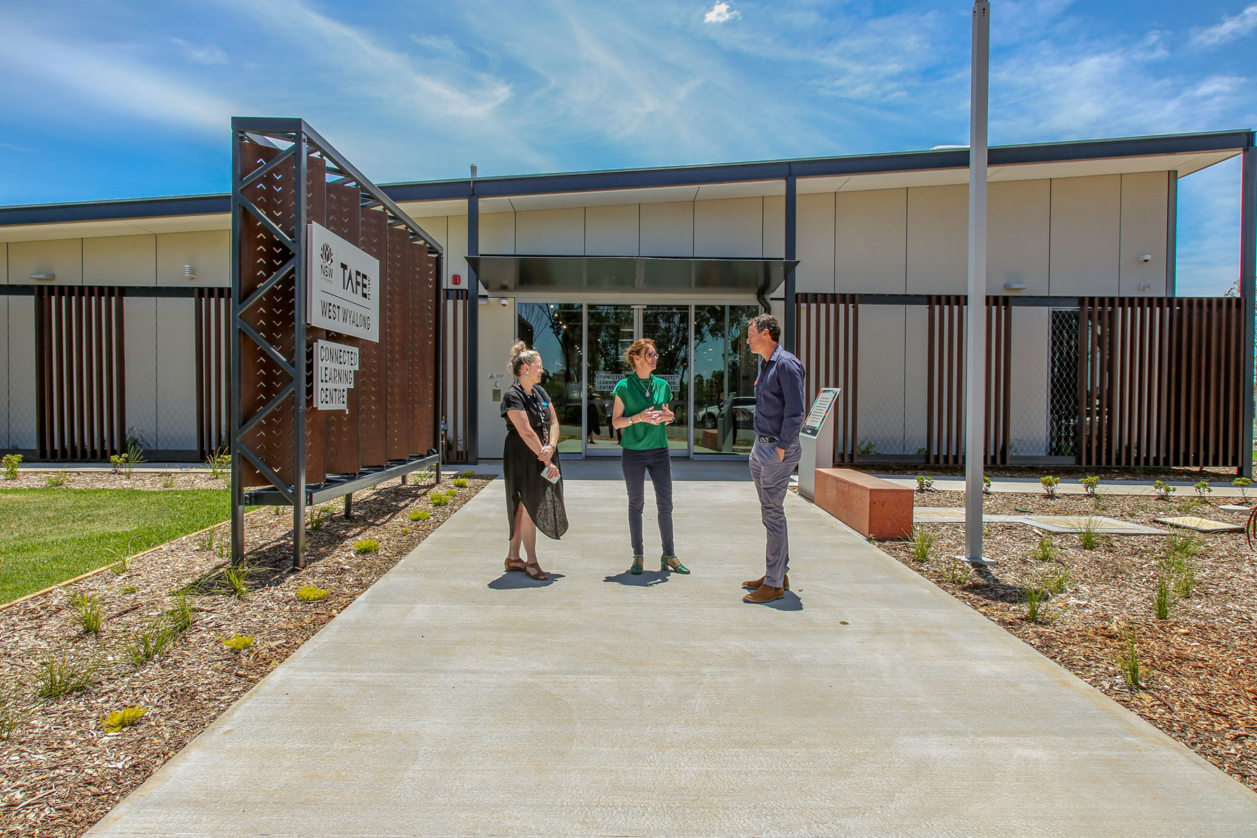 Kate Braunberger, Steph Cooke and Nathon Irvin stand in front of the new building.