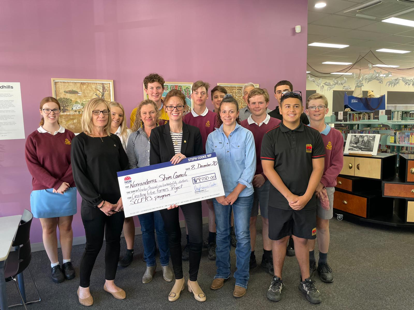 A group of young people stand behind Tammy Galvin and Steph Cooke, who hold a large cheque.