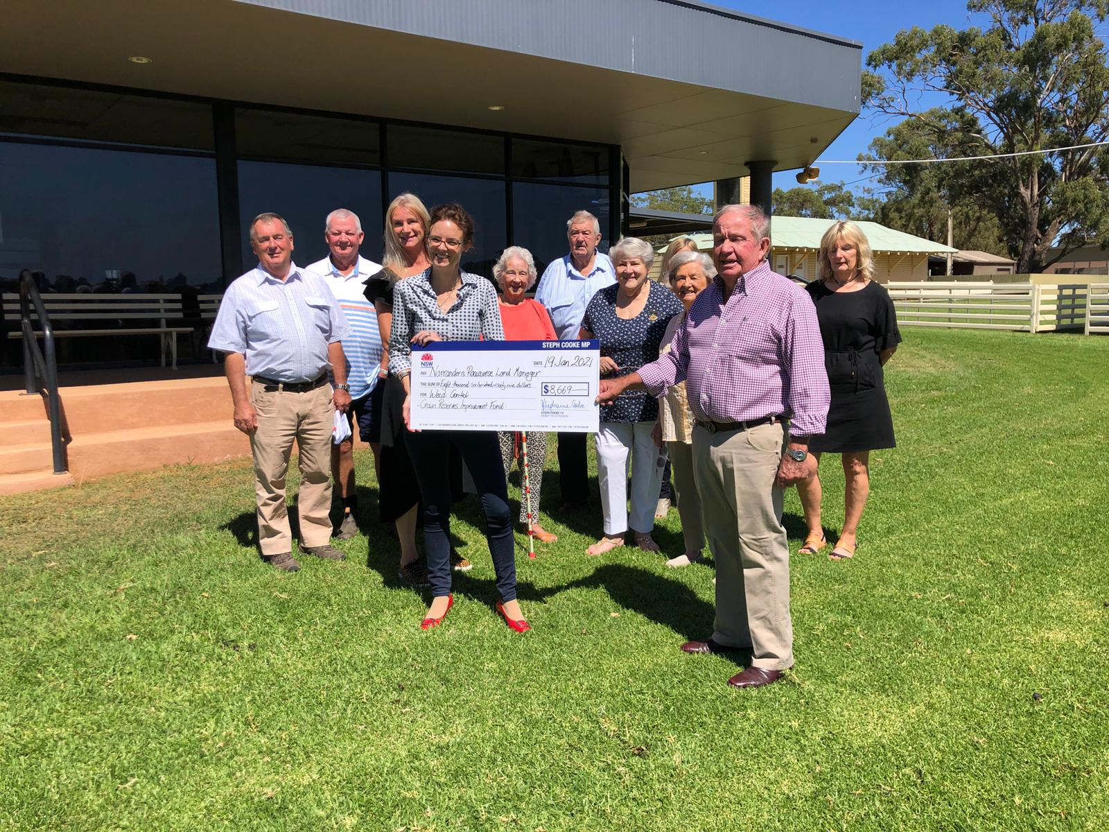 Steph Cooke presents a cheque to a group of people.