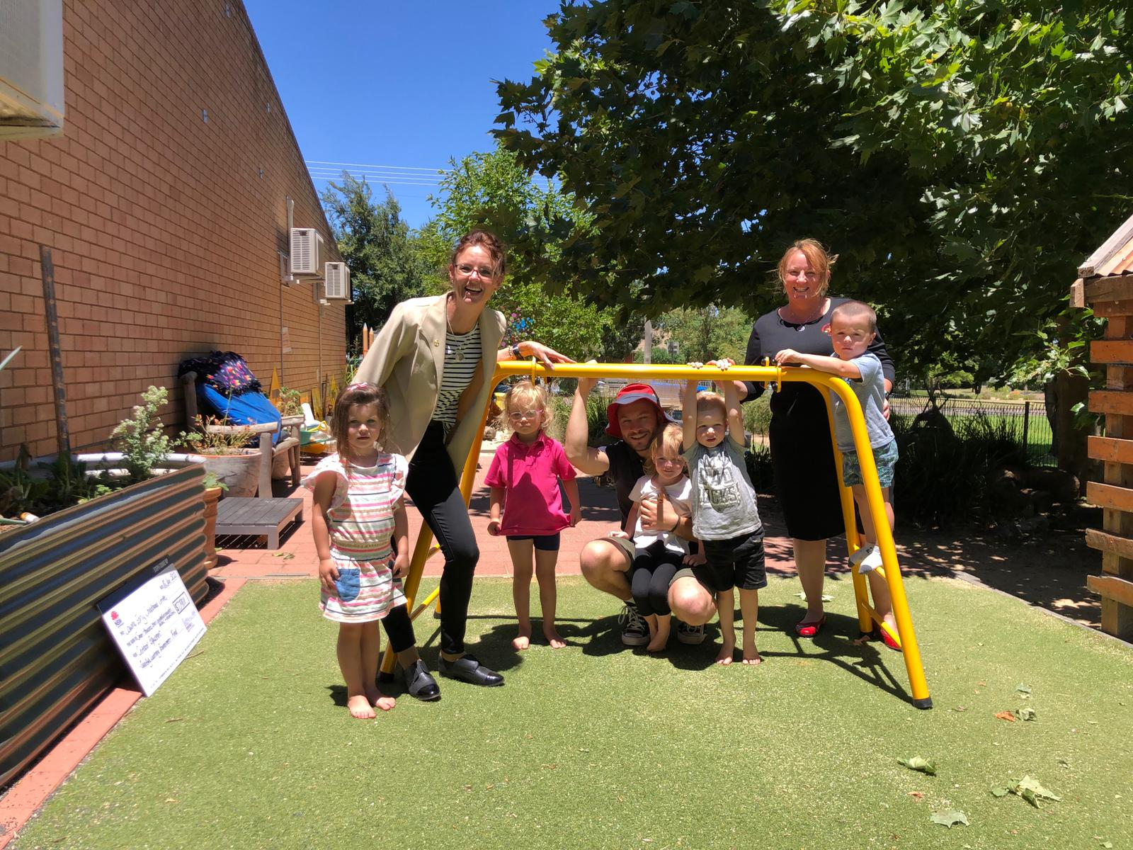 Steph Cooke and Sussan Callaghan stand with small children around a bright yellow climbing frame.