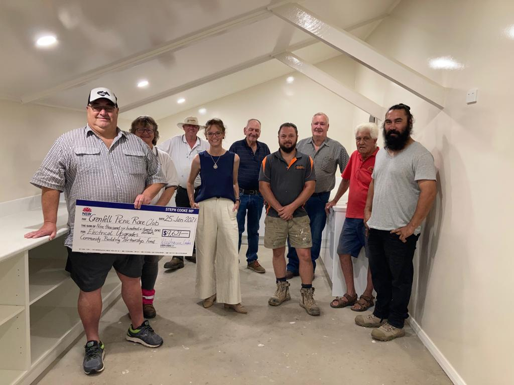 Danny Kotel , Dot Schneider, Thurston Skinner, Steph Cooke MP, Geoff McClelland, Daniel Lennane, Patrick Hazell, Terry Carroll and Phil Napier hold a large cheque and stand in a bright, white room with low beams from the ceiling.