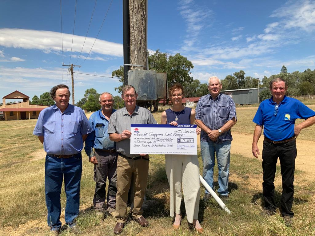 Phillip Walmsley, Rob Ricketts, Stanley Hazel, Steph Cooke MP, Mo Simpson and Jeff Richardson hold a large cheque and stand in front of a power pole.