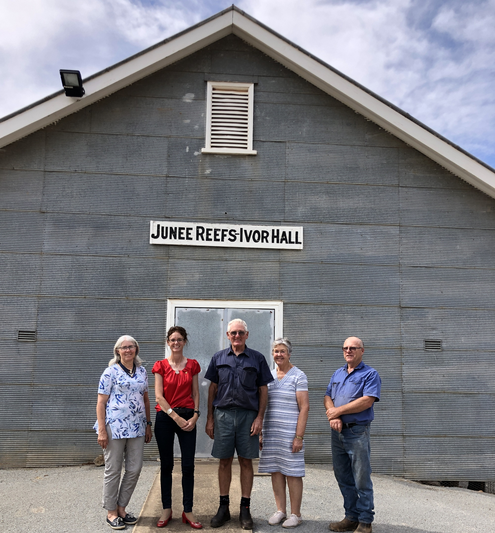 Janice Brabin, Steph Cooke, George Barbin, Margaret Drum and Robert Hillam stand in front of a metal wall with a sign above them reading Junee Reefs Ivor Hall.