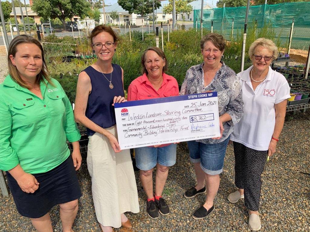 Melanie Cooper, Steph Cooke MP, Jan Diprose, Lorraine Seery and Pam Livingston hold a large cheque and stand in front of trays of native plants.