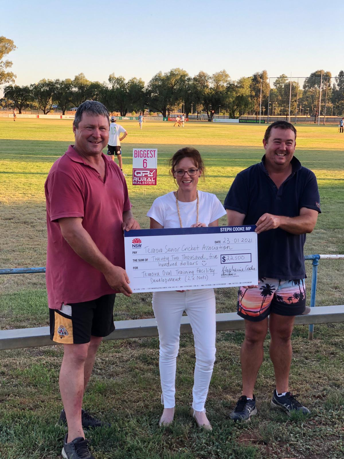 Peter Stimson, Steph Cooke MP and Lincoln Macauley hold a large cheque and stand in front of a sports oval with cricket nets seen in the background.