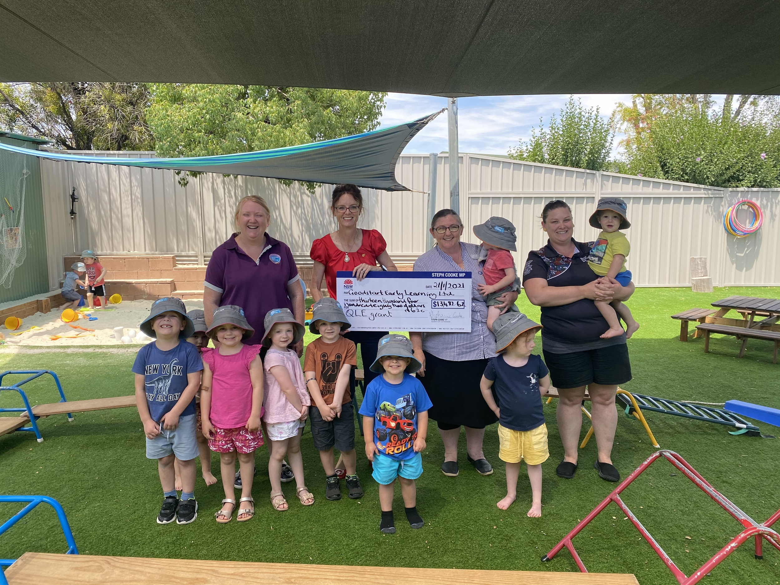 Steph Cooke and Elizabeth Robbie hold a large cheque between them and stand surrounded by staff and students at the early learning centre outdoor area. They are surrounded by play equipment.