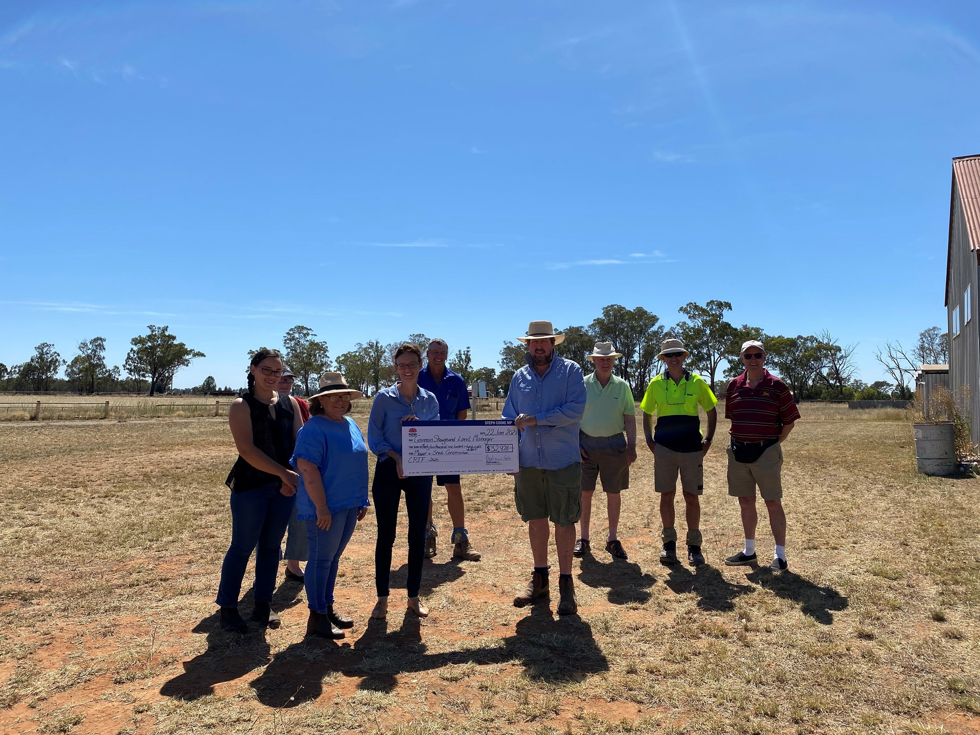 Steph Cooke and members of the Ganmain Showground land management committee stand outside on grass and hold a large cheque.